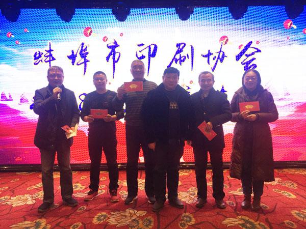 蚌埠市印刷协会副会长、蚌埠市兴顺彩印厂总经理周兴平(中)登台抽奖,并与获奖人员合影留念
