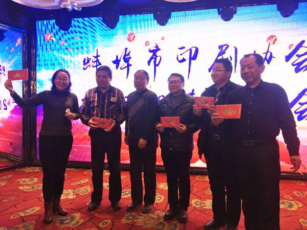 蚌埠市印刷协会副会长、蚌埠市东方彩色印刷厂总经理徐兴国(中)登台抽奖,并与获奖人员合影留念