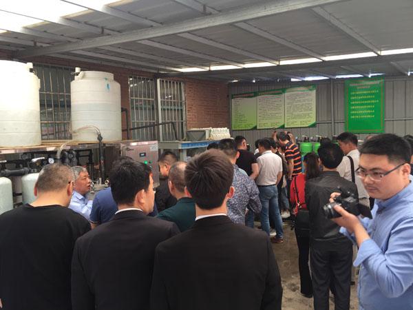 与会人员正在泰兴广力机械厂董事长徐贵山的介绍下,认真参观新环保设备的运行情况
