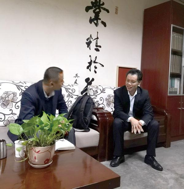 吴勇总经理(右)正在向笔者介绍快马印务公司最新发展情况