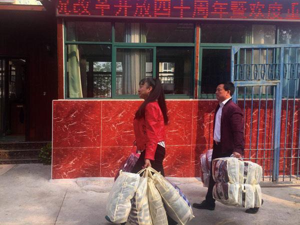 慰问团成员手拎慰问物品正大步走向惠康汉生老年公寓