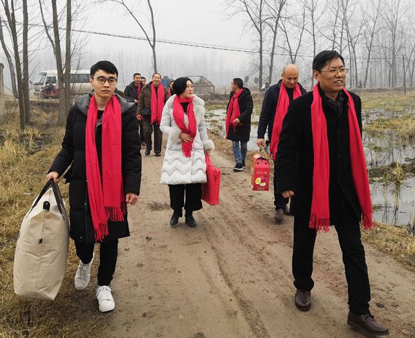 商会慰问团成员在熊桂祥会长的带领下,手拎慰问物品,正踏着乡间泥土路走向慰问特困户家中