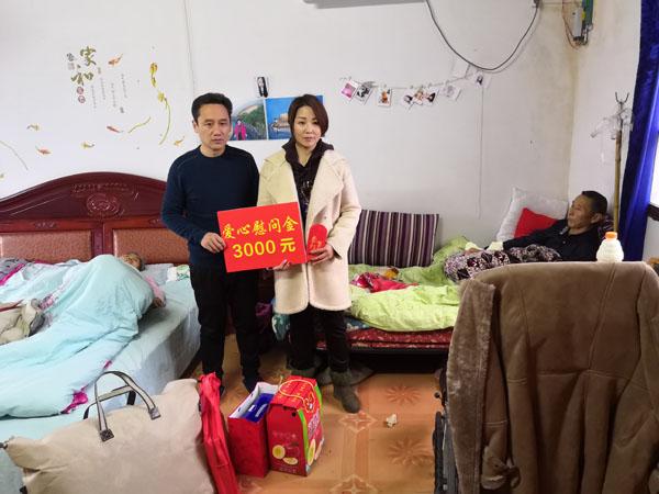 杨白林夫妇双双卧病在床,其一双儿女代为接受慰问金和慰问物品