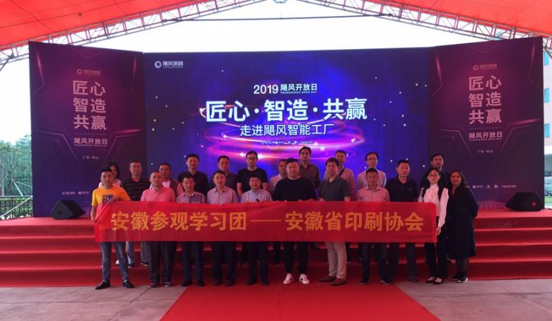 观展团部分团友在飓风网集团旗下的富日智能工厂开放日活动展台前合影