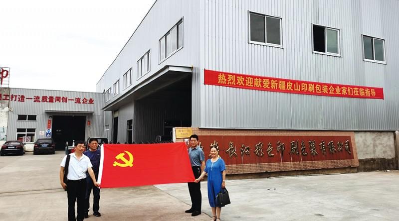 参加此次活动的四位党员手握鲜红的党旗在长江公司大门前合影留念