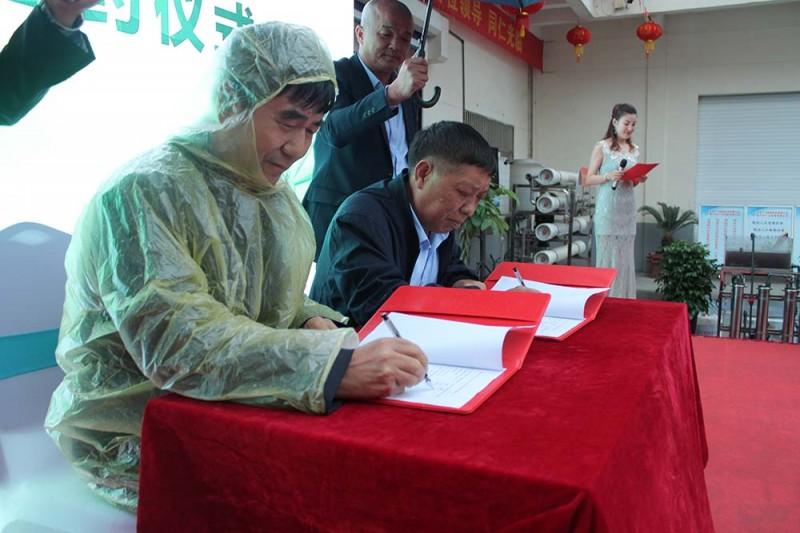 广力总裁徐贵山与河北省唐山市润丰印务有限公司董事长薄会川(穿雨衣者)在《购机协议书》上签名